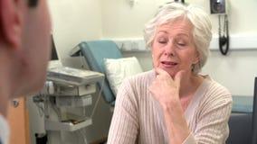 Γιατρός στη χειρουργική επέμβαση που μιλά με τον ανώτερο θηλυκό ασθενή απόθεμα βίντεο