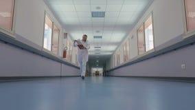 Γιατρός στο άσπρο παλτό και στηθοσκόπιο γύρω από το λαιμό του απόθεμα βίντεο