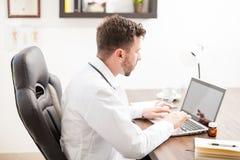 Γιατρός στο παλτό εργαστηρίων που λειτουργεί σε ένα lap-top Στοκ εικόνες με δικαίωμα ελεύθερης χρήσης