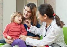 Γιατρός των ώριμων παιδιών που εξετάζει το μωρό στοκ φωτογραφίες