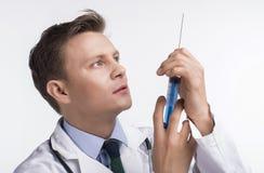 γιατρός φωτογραφικών μηχανών ανασκόπησης που απομονώνεται να φανεί αρσενικό λευκό στηθοσκοπίων του s Στοκ Εικόνα