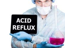 Γιατρός χειρουργικό σε ομοιόμορφο, κρατώντας τη ρόδινη φιάλη και το ψηφιακό PC ταμπλετών με το όξινο reflux σημάδι τεχνολογία Δια στοκ εικόνα με δικαίωμα ελεύθερης χρήσης