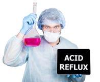 Γιατρός χειρουργικό σε ομοιόμορφο, κρατώντας τη φιάλη και το ψηφιακό PC ταμπλετών με το όξινο reflux σημάδι τεχνολογία, Διαδίκτυο στοκ φωτογραφία
