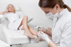 Γιατρός Podiatrist που φροντίζει για το πόδι πελατών με το ειδικό εργαλείο σιδήρου Στοκ εικόνα με δικαίωμα ελεύθερης χρήσης