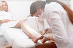 Γιατρός Podiatrist στο λευκό που κάνει τη διαδικασία στιλβωτικής ουσίας για το πόδι Στοκ φωτογραφία με δικαίωμα ελεύθερης χρήσης