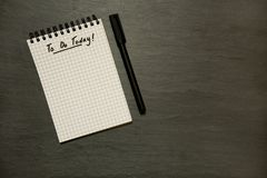 Για να κάνει σήμερα τον κατάλογο σχετικά με το gridded σπειροειδές σημειωματάριο με τη μάνδρα, επείγουσα - στη σκοτεινή πλάκα στοκ φωτογραφίες