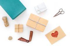 Για να τυλίξει το δώρο Κιβώτιο, έγγραφο του Κραφτ, φάκελος, λεπτό σκοινί, ευχετήρια κάρτα, κορδέλλα, sciccors στην άσπρη τοπ άποψ Στοκ φωτογραφία με δικαίωμα ελεύθερης χρήσης