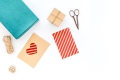 Για να τυλίξει το δώρο Κιβώτιο, έγγραφο, φάκελος, λεπτό σκοινί, ευχετήρια κάρτα, κορδέλλα, sciccors στην άσπρη τοπ άποψη υποβάθρο Στοκ Εικόνα