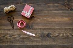 Για να τυλίξει το δώρο Κιβώτιο, λεπτό σκοινί, κορδέλλα, sciccors στην ξύλινη τοπ άποψη υποβάθρου copyspace Στοκ Εικόνες
