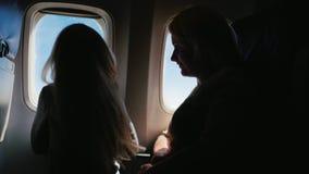 Για να χαρούν μαζί, στο ταξίδι με τους γονείς Το Mom και η κόρη εξετάζουν το παράθυρο του αεροπλάνου για 6 έτη κοιτάξτε φιλμ μικρού μήκους