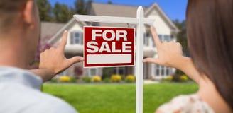 Για το σημάδι πώλησης, το σπίτι και τα στρατιωτικά πλαισιώνοντας χέρια ζεύγους Στοκ Εικόνα