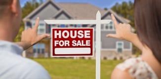 Για το σημάδι πώλησης, το σπίτι και τα στρατιωτικά πλαισιώνοντας χέρια ζεύγους Στοκ εικόνες με δικαίωμα ελεύθερης χρήσης