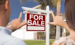 Για το σημάδι πώλησης, το σπίτι και τα στρατιωτικά πλαισιώνοντας χέρια ζεύγους Στοκ Εικόνες
