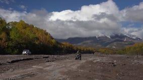 Για όλα τα εδάφη οδήγηση οχημάτων στο δρόμο υποστηριγμάτων στον ξηρό ποταμό στην κατεύθυνση του ηφαιστείου απόθεμα βίντεο
