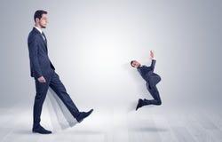 Γιγαντιαίος επιχειρηματίας που κλωτσά έξω λίγο επιχειρηματία Στοκ φωτογραφία με δικαίωμα ελεύθερης χρήσης
