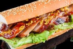 Γιγαντιαίο BBQ σάντουιτς πλευρών με το φύλλο σαλάτας και γαλλική μουστάρδα στο baguette Απομονωμένος σε μια μαύρη ανασκόπηση στοκ εικόνα με δικαίωμα ελεύθερης χρήσης