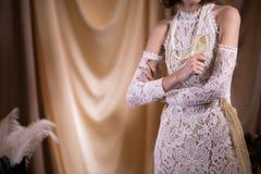 γιορτάζοντας γυναίκα στο άσπρο εκλεκτής ποιότητας φόρεμα ύφους θηλυκή λαβή χεριών Στοκ Φωτογραφία