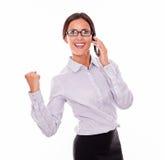 Γιορτάζοντας επιχειρηματίας brunette με το τηλέφωνο κυττάρων Στοκ Εικόνα