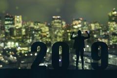 Γιορτάζοντας νέο έτους 2019 σκιαγραφιών επιχειρησιακό άτομο ελπίδας ελευθερίας νέο που στέκεται και που απολαμβάνει στην κορυφή τ στοκ εικόνες