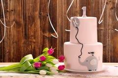 Γιορτή γενεθλίων με το ρόδινο κέικ γενεθλίων και ελέφαντας σε έναν ξύλινο Στοκ Εικόνες