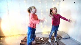 Γιορτή Χριστουγέννων δύο παιδιών που χορεύουν στο σπίτι απόθεμα βίντεο