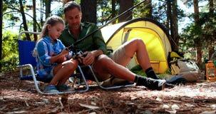 Γιος διδασκαλίας πατέρων στη ράβδο αλιείας χρήσης στο πάρκο φιλμ μικρού μήκους