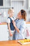 Γιος και νέα μητέρα στην κουζίνα που τρώει το πρόγευμα Στοκ Εικόνες