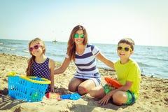 Γιος κορών οικογενειακών μητέρων που έχει τη διασκέδαση στην παραλία Στοκ Φωτογραφία
