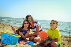 Γιος κορών οικογενειακών μητέρων που έχει τη διασκέδαση στην παραλία Στοκ Εικόνες