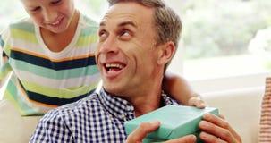 Γιος που δίνει στον πατέρα του ένα αιφνιδιαστικό δώρο στο καθιστικό απόθεμα βίντεο