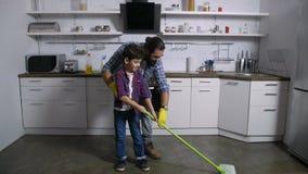 Γιος που βοηθά τον ενιαίο πατέρα με τις εσωτερικές μικροδουλειές απόθεμα βίντεο