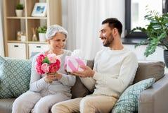 Γιος που δίνει το παρόν και τα λουλούδια στην ανώτερη μητέρα στοκ φωτογραφίες