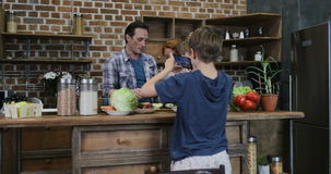 Γιος που κάνει το βίντεο της ευτυχούς οικογένειας να προετοιμαστεί χαμόγελου τροφίμων κουζινών στο μαγειρεύοντας ευτυχές γεύμα απ απόθεμα βίντεο