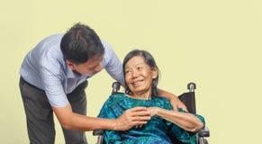 Γιος που φροντίζει την ηλικιωμένη μητέρα στην αναπηρική καρέκλα στοκ εικόνα