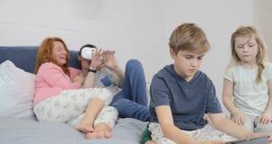Γιος που χρησιμοποιεί την ταμπλέτα ενώ γυαλιά εικονικής πραγματικότητας ένδυσης πατέρων στην κρεβατοκάμαρα, οικογένεια που έχει μ απόθεμα βίντεο