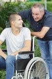 Γιος στην αναπηρική καρέκλα και πατέρας στον περίπατο στοκ φωτογραφία με δικαίωμα ελεύθερης χρήσης