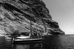 Γιοτ και βάρκες των τουριστών κοντά στους κάθετους απότομους βράχους Acantilados de Los Gigantes Cliffs των γιγάντων στοκ φωτογραφία με δικαίωμα ελεύθερης χρήσης