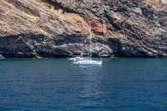 Γιοτ και βάρκες των τουριστών κοντά στους κάθετους απότομους βράχους Acantilados de Los Gigantes Cliffs των γιγάντων στοκ εικόνα με δικαίωμα ελεύθερης χρήσης