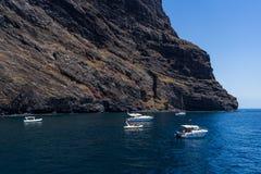 Γιοτ και βάρκες των τουριστών κοντά στους κάθετους απότομους βράχους Acantilados de Los Gigantes Cliffs των γιγάντων στοκ εικόνες
