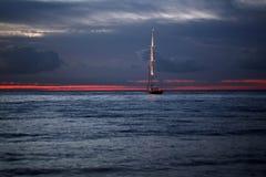 Γιοτ που επιπλέει στη θάλασσα κάτω από το καταπληκτικό ηλιοβασίλεμα Στοκ Εικόνες