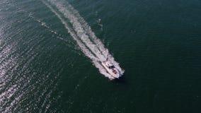 Γιοτ που πλέει στη θάλασσα με τους νέους στη γέφυρα απόθεμα βίντεο