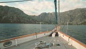 Γιοτ που πλησιάζει τη θάλασσα στα υψηλά βουνά στον ηλιόλουστο καιρό απόθεμα βίντεο