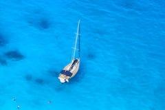 Γιοτ πολυτέλειας ενάντια στην κυανή θάλασσα με τους κολυμπώντας ανθρώπους στοκ φωτογραφία με δικαίωμα ελεύθερης χρήσης