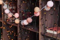 Γιρλάντα ντεκόρ Χριστουγέννων στα ξύλινα shelaves με τα βιβλία νέο έτος παραμονής του 2009 Στοκ Φωτογραφίες