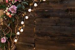 Γιρλάντα των λουλουδιών και των λαμπών φωτός και μια σύνθεση των κλαδίσκων σε ένα ξύλινο υπόβαθρο Στοκ εικόνα με δικαίωμα ελεύθερης χρήσης