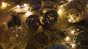 Γιρλάντα Χριστουγέννων κινηματογραφήσεων σε πρώτο πλάνο και χειροποίητες σφαίρες σε ένα playd με τα χρυσά φω'τα Έννοια Χριστουγέν απόθεμα βίντεο