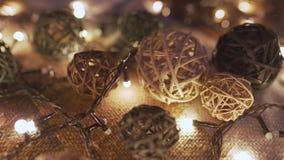 Γιρλάντα Χριστουγέννων κινηματογραφήσεων σε πρώτο πλάνο και χειροποίητες σφαίρες σε ένα playd με τα χρυσά φω'τα Έννοια Χριστουγέν φιλμ μικρού μήκους