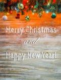 Γιρλάντα χριστουγεννιάτικων δέντρων με τη διακόσμηση στον ξύλινο πίνακα Φωτεινά Χριστούγεννα και νέο υπόβαθρο έτους με το κείμενο Στοκ Εικόνες