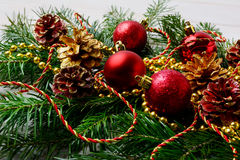 Γιρλάντα Χριστουγέννων με τις κόκκινες διακοσμήσεις και τους χρυσούς κώνους πεύκων Στοκ εικόνα με δικαίωμα ελεύθερης χρήσης