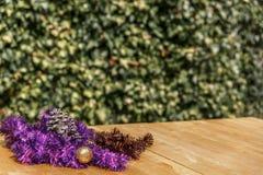 Γιρλάντες, σφαίρα Χριστουγέννων και pinecone στον ξύλινο πίνακα στο μέτωπο Στοκ Φωτογραφία